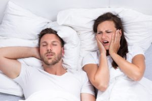 woman frustrated with man's snoring