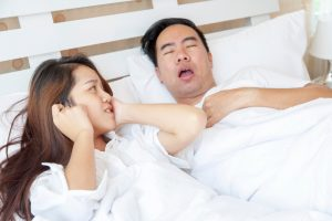 sleeping man snores while woman plugs her ears